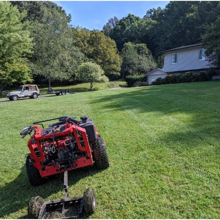 Commercial lawn mower in a large front yard with a with the work truck and trailer in the customer's driveway.