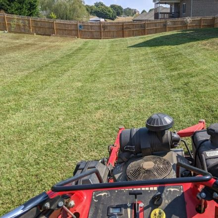Commercial lawn mower in a large back yard with a fence during a residential mowing service.